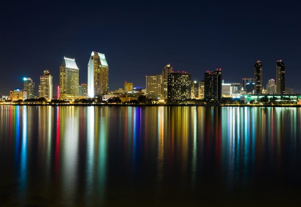 Skyscrapers along the bay in San Diego at night by Booking Express Travelr4